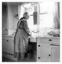 probably around 1930's.. an old farmhouse kitchen. Note the counter slanted towards the sink for water runoff..