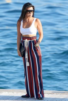 Kourtney Kardashian wearing Bvlgari Serpenti Snake Watch, Celine Flap Clutch, Celine Adele 41377 Sunglasses and Tularosa Keeton Pants