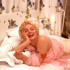 Marilyn Monroe in a bed holding a red rose