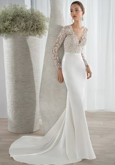 This sleek luxe satin sheath gown features a lace bodice with a plunging V-neckline and long lace sleeves. Transitioning to a high back with button closures and a sophisticated Chapel length train.