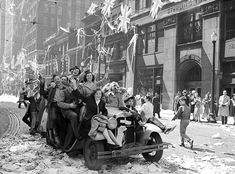 Victory In Europe Day (8th May,1945) Cheering people sit in and on a car, waving flags. (Toronto)