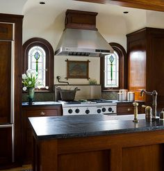 Love the windows - These mahogany kitchen cabinets feature full inset doors and drawers and brass bin pulls. The cabinet's rich dark color, Craftsman lines, and Black Brazilian soapstone counters suit the overall design goal of choosing everything to suit a Mission Revival bungalow built in the 1920s.