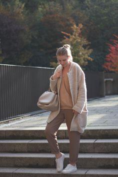 Gemütliches Herbstoutfit in nude Tönen. Beige Stoffhose mit weißen Sneakern, rosa farbenem Pullover im Wickeldesign und kuscheligem Teddy Mantel in Creme. Dazu eine schöne Tasche in beige mit Henkel. www.mondodellamoda.de --> mehr Inspirationen und Outfits