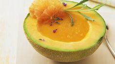 Kurz vor dem Servieren das Lavendelöl einrühren und die kalte Suppe in die kalten Melonenhälften füllen. Mit Orangenscheiben und Lavendelblüten garniert servieren: Melonensuppe in der Melone | http://eatsmarter.de/rezepte/melonensuppe-in-der-melone