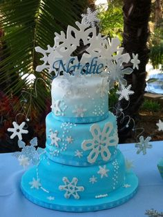 Winter Wonderland - Winter wonderland party, snowflake themed cake to go with.  Sugar paste and poured sugar snowflakes, painted with rainbow disco dust and coarse sugar.  Covered in fondant airbrushed blue gradient to white Acrylic name is a Custom ordered name topper