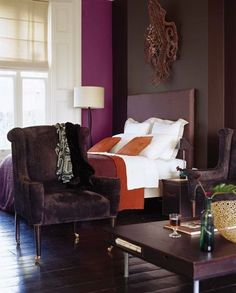 Orange and purple is an unexpected colour combination that is just so good | via Apartment Therapy | Deep purple bedroom with dark wooden floors and painted walls | deep purple headboard, orange cushions and purple bedspread | white bedlinen | aubergine velvet armchair | Get the look with an IKEA Abelvar headboard with a Bemz cover