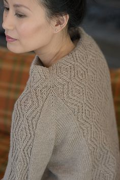 A wide panel of traveling twisted stitches forms both the stand-up collar and main body of this sweater from designer Allison Jane. The stitch pattern is mirrored in the sleeves, which are shaped with raglan increases.