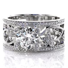A magnificent piece that is all sparkle, Design 2297 features a 1.25 carat round center stone. The unique wide band features a floral pattern and lots of micro pave side stones; you'll be mesmerized by them. Each of the prongs even has a single small diamond set into it surrounded by milgrain!