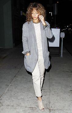 Rihanna wears a leopard print t-shirt, gray oversized blazer, cropped khaki pants, peep-toe booties, and gold jewelry