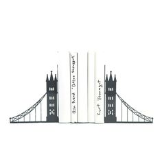 """Decorative Bookends London bridge. Cool Home Decor Gift for Housewarming Party. Gift for reader. Stylish bookshelf decor. Unique metal bookends - An Icon of London landscape. London bridge. Our take on it in bookends. What do you think? Powder coated laser cut metal. The bookends have anti slippery silicon pads for additional furniture protection. ↳ One pair of metal bookends ↳ 5.9"""" x 4.3"""" and 4.7"""" ↳ 15 x 11 x 12 cm ↳ Holds a long row of books ↳ FREE WORLDWIDE SHIPPING ✈ We choose the…"""