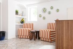 A pair of chunky, orange-striped chairs also feature in the lobby, which is anchored by a grooved timber concierge counter. Blue Striped Curtains, Striped Chair, Wooden Side Table, Wicker Chairs, Hotel Interiors, Antibes, South Of France, White Walls, Furniture