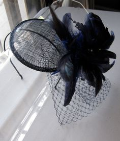 Navy Blue Feather Flower Sinamay Fascinator Hat with Veil and Satin Headband, for weddings, parties, cocktail, special occasions. $65.00, via Etsy.