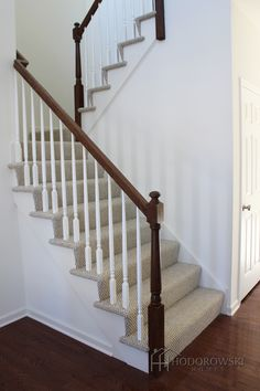 Dark floors with a matching post and classic white colonial spindles.