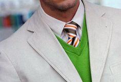 Light grey jacket, grey pinstripe shirt, brown/orange/white/blue stripe tie, green sweater vest