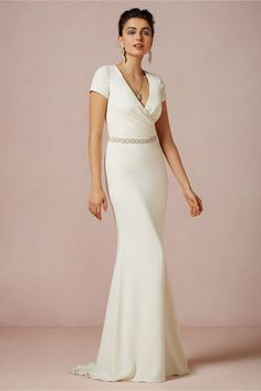 "Isis Gown $800.00 STYLE: 28753119  We love the stunning simplicity of this ivory crepe gown, from the elegant surplice neckline to the soft, trumpet silhouette. To add a dash of something extra, replace the satin sash with a bejeweled belt. From Badgley Mischka. Back zip. Polyester stretch crepe; polyester charmeuse lining. Dry clean. Imported. Badgley Mischka exclusive for BHLDN Falls 47"" from natural waist"
