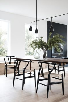 In the dining room of an Amagansett residence, Hans Wegner wishbone chairs gather around a Jupiter dining table by Casey Dzierlenga, crowned by a Twig 5 light fixture by Apparatus.