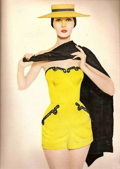 Dovima wearing a yellow playsuit with black lace details, 1950s.