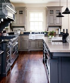 """The kitchen's colour scheme contributes to its 19th-century flavour...the couple used a deep charcoal shade that makes the feature a focal point but doesn't overwhelm the green-toned kitchen cabinetry."""