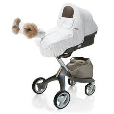 Winter white baby stroller with fleece mittens on handle.