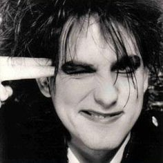 Robert Smith pointing fingers to head