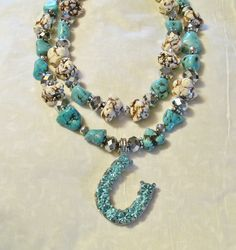 A Born In The Barn Design... handmade necklace. Double strand of white and turquoise with silver accents on a rhinestone horseshoe
