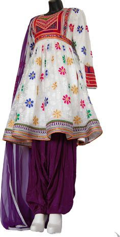 This traditional white Afghan dress includes a hand embroidered skirt and a matching purple pant and scarf. The fabric is textured with a colorful floral pattern. This dress was meticulously hand made and features a Kuchi inspired look. Afghan Clothes, Afghan Dresses, Hijab Fashion, Fashion Dresses, Women's Fashion, Pakistani Outfits, Indian Outfits, Etsy Embroidery, Traditional Clothes