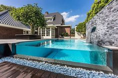 Swimming Pool, Attractive Waterfall Feature On The Natural Stone Wall Design In Amazing Glass Swimming Pool Design Combined With Natural Stone Decoration And Wooden Floor Also Natural Green Trees In Classical Cozy House: Relaxation Time In Eye Catching Swimming Pool Design