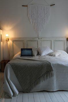 Makuuhuone ja valkoinen moderni ryijy. Sängynpäätynä vanha ovi! 50-luvun talo, sisustus, valkoinen, maalaisromantiikka