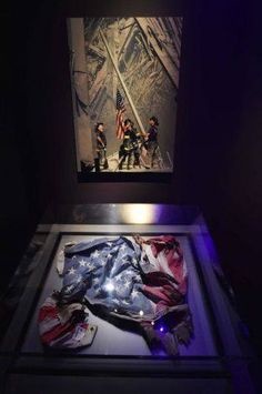An American flag found in the rubble is displayed under the now iconic image of a flag being raised by firemen at the World Trade Center site by Thomas E. Franklin of The Record. Remembering September 11th, 11. September, Memorial Museum, Independence Day History, American History, American Flag, 911 Never Forget, Don't Forget, Live Action