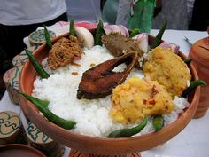Panta Ilish - a traditional platter of Panta bhat with fried Ilish slice, supplemented with dried fish (Shutki), pickles (Achar), dal, green chillies and onion - is a popular serving for the Pohela Boishakh festival. — at People's Republic of Bangladesh.