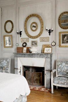 Dominującą w sypialni tkaninę Charles dobrał do oryginalnego potralu kominkowego z szarego marmuru.