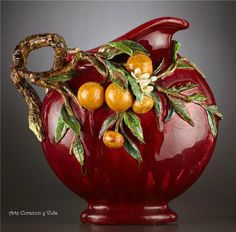 Oranges, naranjas, on a beautifully rotund ruby colored majolica pitcher.