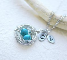 Personalized bird nest necklace. Two eggs in the nest. Two personlalized initials.  The bird nest wrapped with silver tarnish resistant wires. Two turquoise stones are perfectly nestled. Very cute necklace! Great gift for mother, grandmom, birthday, sister, anniversary, familly...  1. Nest pendant: about 25mm long. Nest can be made with 1, 2, 3, 4.5 eggs. Please select the color of eggs you like from the 4th photo. 2. Initial leaves: hand stamped letter of your choice. Please leave your…