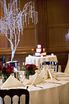 Ivory linens and napkins paired with cranberry floral arrangements and large silver tree with hanging crystals   villasiena.cc