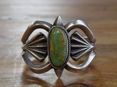 Gorgeous vintage Navajo sterling silver sandcast cuff bracelet with a stunning green turquoise stone in the center. The cuff measures about 5 1/2 on the inside, with a 1 gap. The face of the bracelet is about 2 tall. The turquoise stone measures about 1 1/8 tall and 1/2 wide. This piece is marked AA Sterling. Beautiful sandcast piece!
