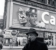 Gene Baumwoll Times Square, Camel Sign - 1964, Camel Sign in Times Square, 1964. One of the most enduring images of Times Square is the Camel Man, who blew smoke rings around the clock for decades from a billboard mounted on the Claridge Hotel on Broadway between 43rd and 44th Streets. During World War II, the image switched from soldiers to sailors to airmen....   billboard-one.jpg (400×358)