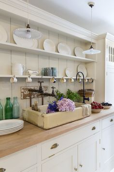 The open shelves provide plenty of display space: They're lined with Royal Stafford creamware in a revived pattern called Honest, available exclusively from the shop. Modeled after 18th-century cabinet hardware, the brass button and cup pulls were sand cast in the UK by one of Plain English's secret sources.