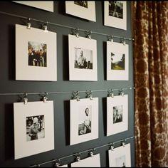 Une galerie photo originale pour la décoration d'un couloir ! Les photos sans cadre sont suspendues par des crochets à un fil d'acier tendu. Plus