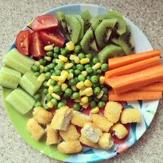 Chicken nuggets, cucumbers, tomatoes, kiwi, carrots, peas and corn. #toddlermeal