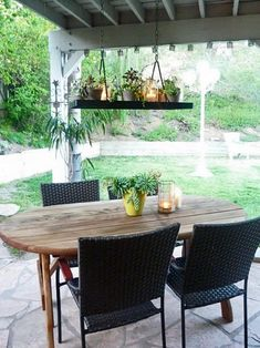 """When your pot rack just doesn't seem to suit the kitchen anymore, take it outdoors. Blogger Erin Lepperd revamped a hanging pot rack in her outdoor space by arranging potted plants, succulents and tea lights inside Mason jars. Suspended over her dining table, the new """"chandelier"""" is whimsical, organic and perfect for alfresco entertaining."""
