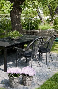 Here's proof that an outdoor dining area as a part of your landscape design doesn't have to be elaborate.  This table with wrought iron chairs has been set in gravel (nice touch - no mud, no weeds underneath) under a shady tree, and accented with potted flowers in baskets.  For outdoor room design in Minneapolis MN, visit us at http://www.aldmn.com