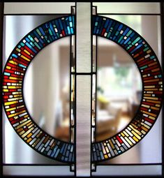 Internal stained glass panel, East Kilbride. Designed for a modern house linking the stairwell to the main living area. Etched and bevelled glass used to to contrast with the opalescent and hand made coloured Lamberts glass of the circle. Size 1000mm x 1000mm.