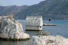 A Lycian rock-cut tomb, memento of the mysterious and long-lost ancient culture of Lycia in southern Turkey, stands half-submerged in the Mediterranean Sea