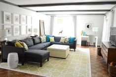 The gorgeous living room at Young House Love with sectional sofa, ottoman and wood TV console