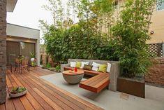 Remek egyedi kültéri bútor bútor a betonból és fából épített pad, a hozzá passzoló kerek beton asztallal. A pad mögött bambusz sor, a növénytartó corten acél.