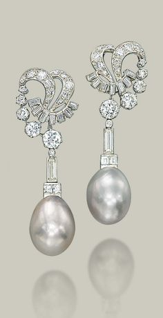 A PAIR OF NATURAL PEARL AND DIAMOND EAR PENDANTS Each greyish white natural drop-shaped pearl, measuring approximately 13.7-14.8 x 19.1 mm and 13.8-14.5 x 19.0 mm, with a square and baguette-cut diamond surmount, to the baguette and brilliant-cut diamond openwork scroll top, late 1960s, mounted in platinum and gold, 6.0 cm