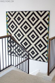 """When faced with a giant blank space, you might think """"gallery wall!"""" And then you might think again when you realize how much work (and money) hanging tons of frames will be. Enter this large, graphic rug which fills the space in minutes — for less than $100. Click through for more on this and other IKEA rug hacks."""