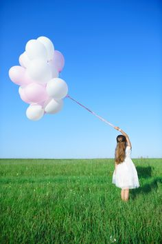 Girl holding balloons on a summer day.