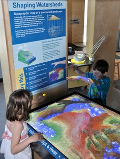 "ECHO Lake Aquarium and Science Center - ""Shaping Watersheds Interactive Sandbox"" - augmented reality sandbox interactive. Participants run their hands through real sand, forming mountains, lakes and rivers, while a 3-D camera and digital projector allow users to create virtual topography in real time, make it ""rain"" and watch where the water flows. Shows in living color how water moves and interacts with the landscape to create watersheds."