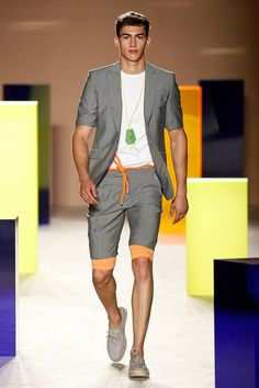 Toller hellgrauer Zweiteiler mit Kurzarmsakko und Shorts, schön kombiniert mit orangefarbenen Accessoires. | Antonio Miró